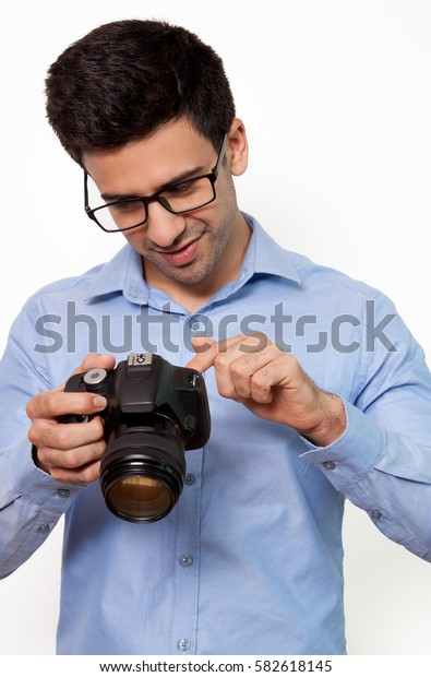 Busy man in eyeglasses watching photos on camera