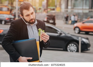 Busy man is in a hurry, he does not have time, he is going to eat snack on the go. Worker eating, drinking coffee, talking on the phone, at the same time. Businessman doing multiple tasks