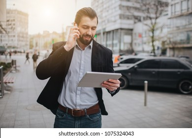 Busy man is in a hurry, he does not have time, he is going to talk on the phone on the go. Businessman doing multiple tasks. Multitasking business person.