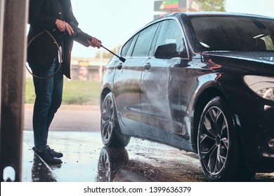 Busy man in jeans and blaser is washing his own car at car washing station.