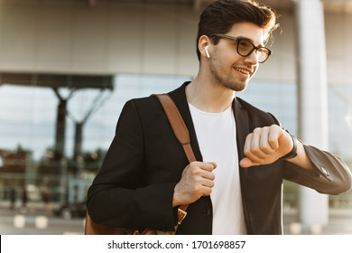 Busy man looks at watch and smiles. Portrait of brunette handsome guy in black jacket and white t-shirt holding brown backpack. Businessman in eyeglasses poses outside.