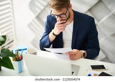 Busy man sitting at desktop and holding papers in hand. He is checking them carefully and precisely
