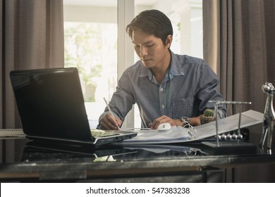 Busy man working at home. man using laptop on desk with smartphone and tablet.