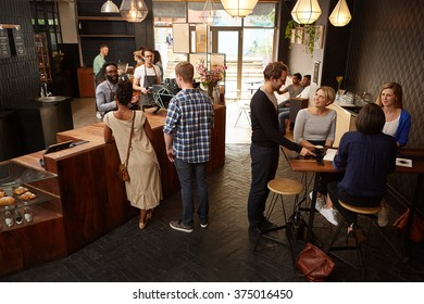 Busy modern coffee shop with customers sitting and ordering