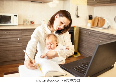 Busy mom writing in notepad while holding a baby