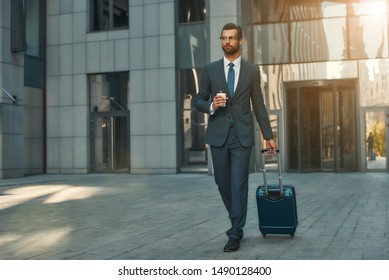 Busy morning. Full length of young and handsome bearded businessman in suit pulling his luggage and holding cup of coffee while walking outdoors