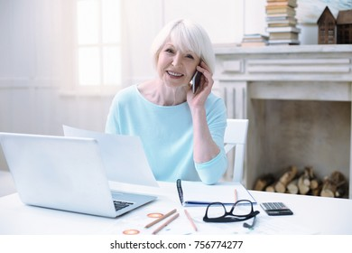Busy morning. Happy emotional active pensioner looking busy while talking on the phone and sitting with a laptop