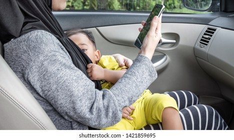 Busy mother give breastfeeding while talking on phone in car.