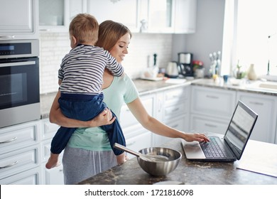 Busy mother holding child and working on laptop - Shutterstock ID 1721816098