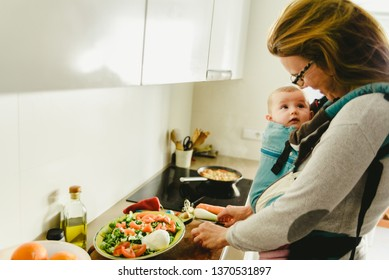 Busy mother preparing food in the kitchen while taking care of her baby, in a baby carrier using the kangaroo method.