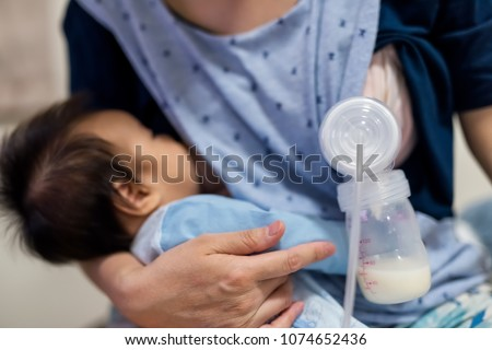 Busy mother pump milk into Automatic breast pump machine and feed breastmilk by another boob to her daughter. Maternity and uncondition love for best healthy nutrition food for newborn baby