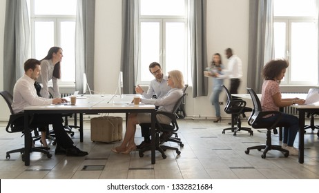 Busy multicultural enterprise employees sitting at desks working on computers in modern office rush, staff business people company workers moving talking in big corporate coworking open space room