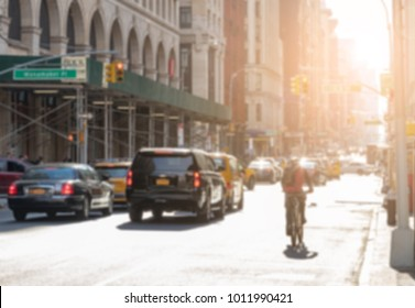 Busy New York City street scene with cars, bike and buildings blurred background