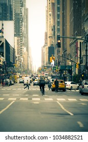 Busy New York City street with cars and pedestrians. Photograph has been edited to alter and blur all faces, trademarks and signs.