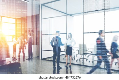 Busy office interior. Group of colleagues are standing near reception counter. Pair of people shaking hands. Concept of business environment. Toned image
