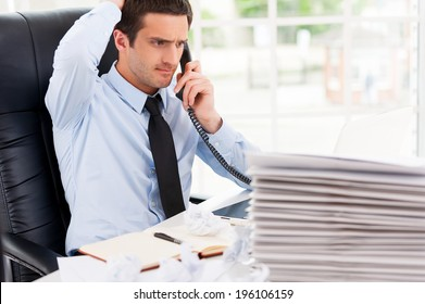 Busy office life. Frustrated young man in formalwear talking on the telephone and holding hand in hair while sitting at his working place