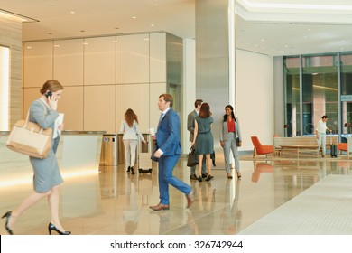 Busy office lobby with business people walking and talking
