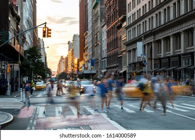 Busy people walk across the crowded intersection on 23rd Street and Fifth Avenue in Manhattan, New York City NYC