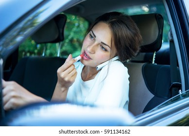 busy pretty girl with lipstick and phone while driving