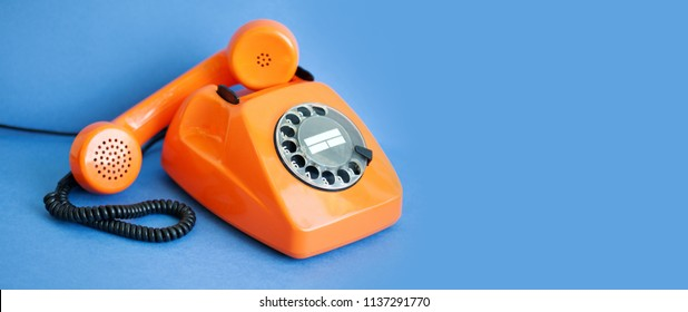 Busy retro phone orange color, handset receiver on blue background. copy space.