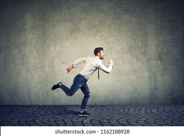 Busy running young business man on gray wall background