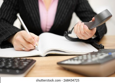 busy secretary is answering call and writing memo at the same time