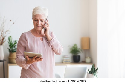 Busy senior woman consulting client on phone and reading contract on digital tablet at home, copy space