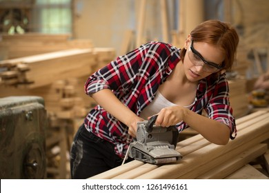 Busy and serious craftswoman grinding timbers with special machine. Beautiful woman with ginger hair wearing safety glasses. Concept of joiner's shop and woodworking.