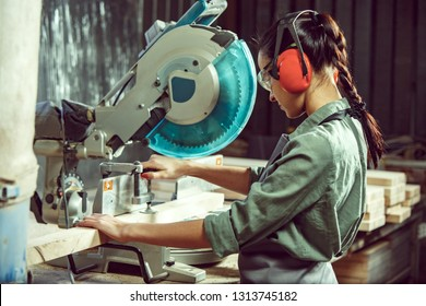 Busy and serious craftswoman grinding timbers with special machine. Beautiful woman wearing safety glasses. Concept of joiner's shop and woodworking. Gender equality. Male profession