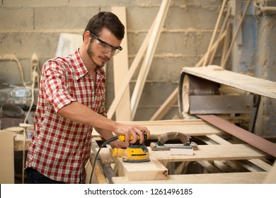 Busy and serious joiner holding yellow sander and working with wood. Professional carpenter in safety glasses standing in joiner's shop. Concept of woodworking and craftsmanship.