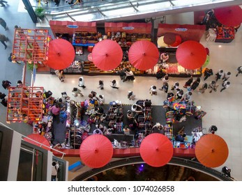 A busy shopping centre in Bangkok, with people and umbrellas viewed from above