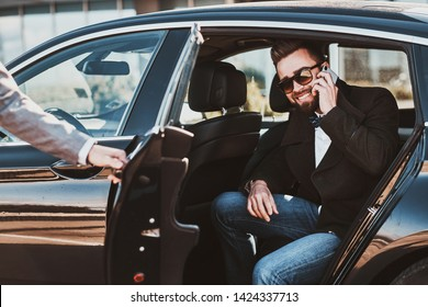 Busy smiling businessman in sunglasses is talking by smartphone while his elegant assistant is opening door for him.
