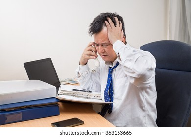 Busy, stressful and frustrated Asian business manager talking on telephone in office