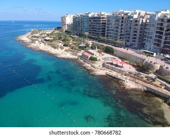 Busy summer beach at Exiles Beach and Bay with Independence Gardens behind, off St Julians Bay and Tower Road Sliema, Malta. Panorama Sliema, view from the height of the bird's eye.