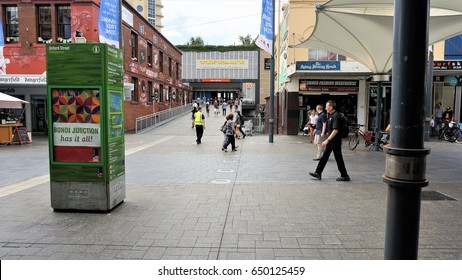 Busy Sydney street on 5 Feb 2016. In view are people, Oxford Street information box, Bondi Junction train station, shops, sign boards, shopping plaza, buildings, graffiti, billboards, street lights