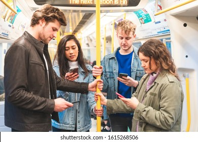 Busy tube, people looking at smartphones and texting - Multiracial group of friends together in subway metro train in London - Travel, lifestyle and commuting in millennials life