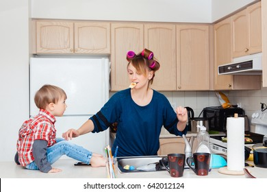 Busy white Caucasian young woman mother housewife with hair-curlers in her hair cooking preparing dinner meal in kitchen, child son boy sitting on table, crazy parent life
