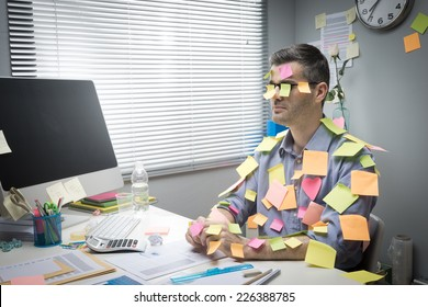 Busy white collar sitting at desk covered with stick notes.