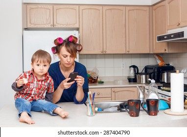 Busy white mother housewife with hair-curlers in her hair surfing Internet chatting on phone in kitchen, her child son boy sitting beside her smiling and playing on his own, crazy busy life concept