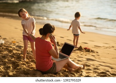 Busy woman being disturbed by child while teleworking at seashore