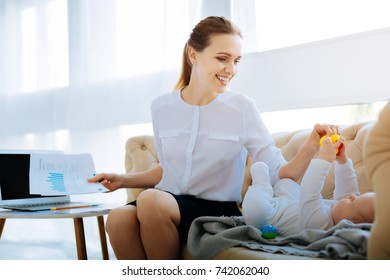Busy woman giving a bright toy to her child