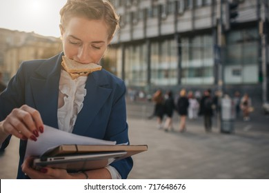 Busy woman is in a hurry, she does not have time, she is going to eat snack on the go. Worker eating and talking on the phone at the same time..  Business female person.