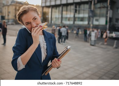 Busy woman is in a hurry, she does not have time, she is going to eat snack on the go. Worker eating and talking on the phone . Businesswoman doing multiple tasks.   Business female person.