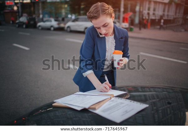 Busy woman is in a hurry, she does not have time, she is going to talk on the phone on the go. Businesswoman doing multiple tasks On the hood of the car. Multitasking business person.