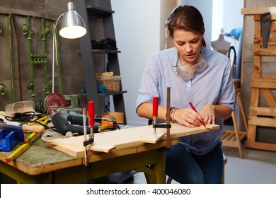 Busy woman tinkering in workshop.