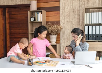 Busy woman trying to work while babysitting three kids.  Young Asian mother on a call with three children playing around her . Working women with multitasking.