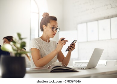 Busy woman using smart phone and laptop having an online business conversation in a cafe or coworking platform, drinking coffee. Business concept.