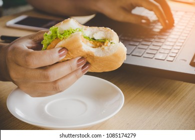 busy woman worker eating junk food burger while working on laptop in office, unhealthy eating lifestyle
