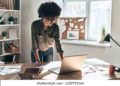 Busy working day. Attractive young African woman working while standing in the office