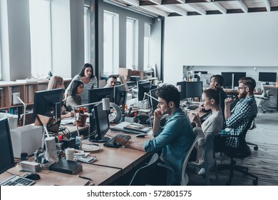 Busy working day. Group of young business people concentrating at their work while sitting at the large office desk in the office together